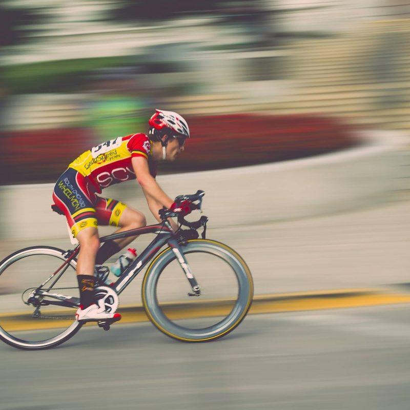 Mies pyöräilee kilpapyörällä kaarteessa kovaa vauhtia.