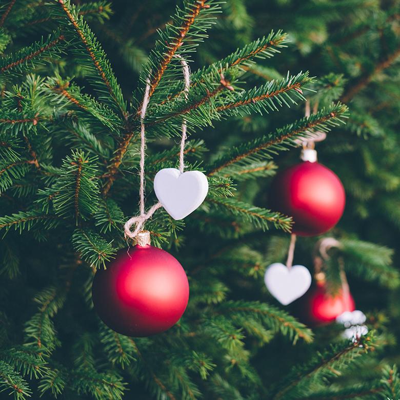 Kuvituskuva joulukuusesta, jossa punaisia palloja