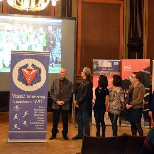 Kuvassa ihmisiä yleisön edessä esittelemässä toimintaa ja Ikurin Vire -seuran roll-up