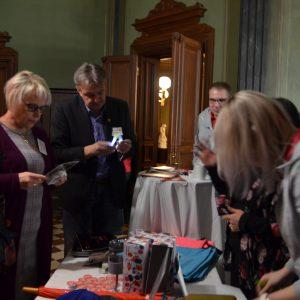Kuvassa ihmisiä katsomassa pöydällä olevia tuotteita