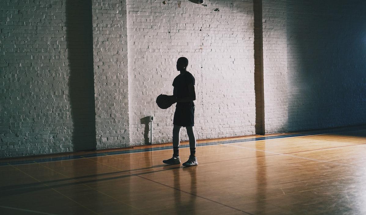 Pimeässä liikuntasalissa yksinäinen poika pitelee koriapalloa käsissään.