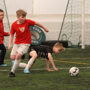 Nuorten poikien jalkapallopelitilanne. Mustassa pelipaidassa pelaava poika on nousemassa maasta ja punaisella pelipaidalla pelaava poika lähestyy palloa.