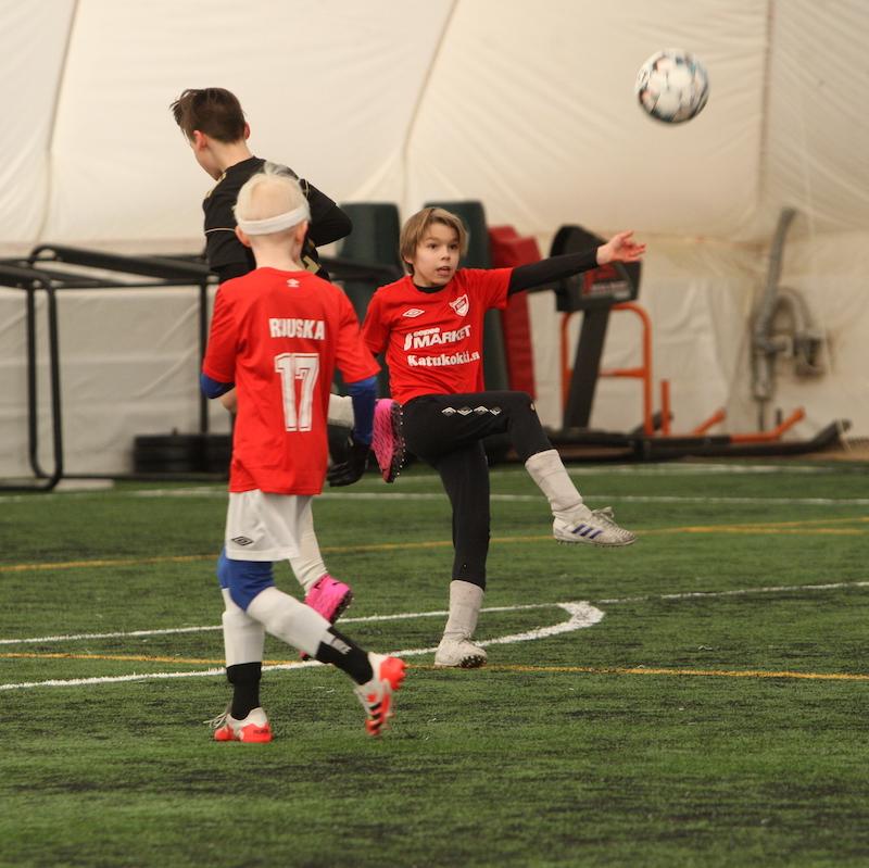 Harrastejalpalloturnaus. Nuori poika on potkaisemassa ilmassa olevaa palloa, volleytä.