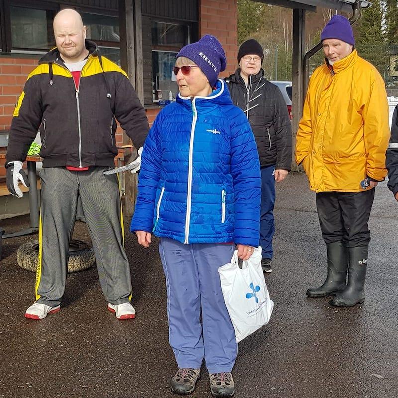 Neljä ihmistä seisoo rakennuksen edessä kisapäivänä. Ihmisillä on yllään tuulelta ja sateelta suojaavat urhieluvaatteet.