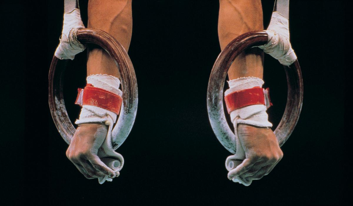 Telinevoimisteluväline renkaat, joissa miesoletetun kädet. Kuvan tausta on musta