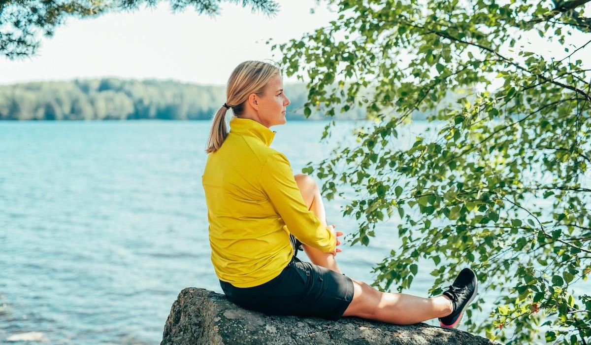 Nainen istuu kivellä keltaisessa paidassa katsellen järvelle