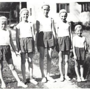 Mustavalkokuva vuodelta 1954 poikia seisoo rivissä juhlavaatteet pääällä