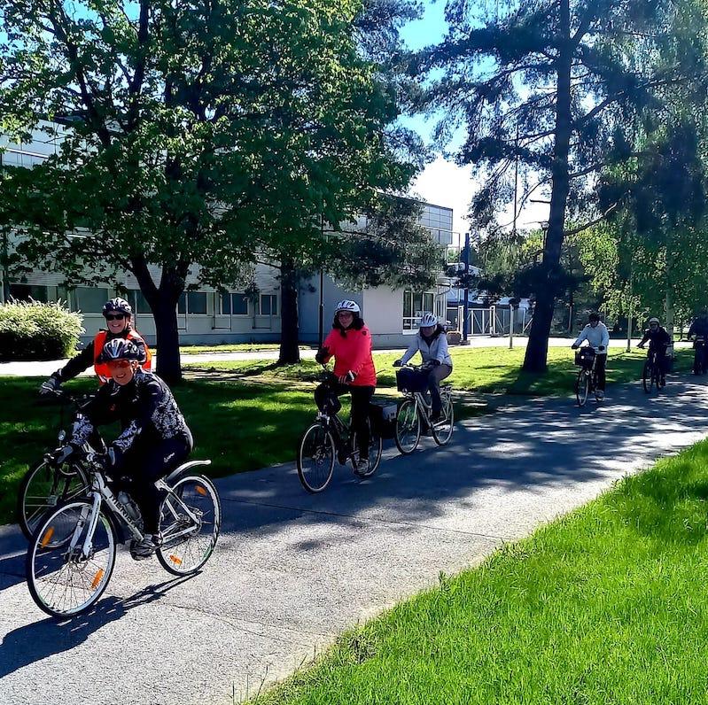 Polkupyöräretkellä pyöräilijät jonossa aurinkoisella säällä.
