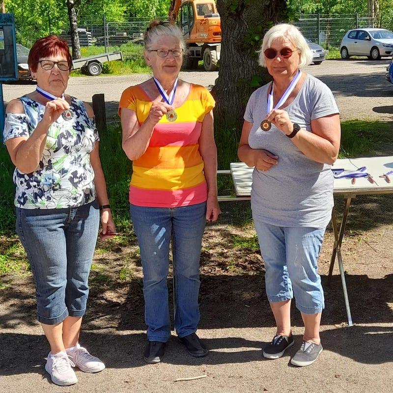 Annalan kentän voittajat naiset. Kolme naista rivissä mitalit kaulassa.