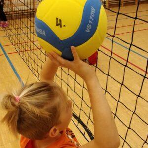 Lentopalloverkko ja lapsi verkolla pallon kanssa.