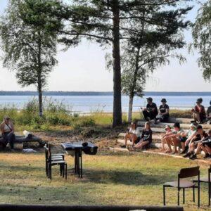 Joukko lapsia ja nuoria kokoontuneena ulkona. Istuvat auringon paistaessa kaaressa.