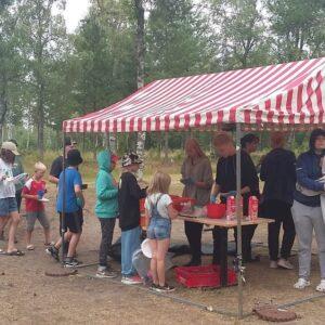 Joukko lapsia ruokajonossa ulkona.