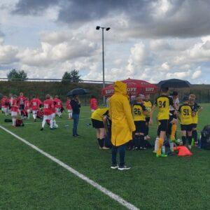 Poikien joukkueet ovat valmiina jalkapallopeliin kentällä. Lapsilla on sateenvarjoja vesisateen vuoksi.