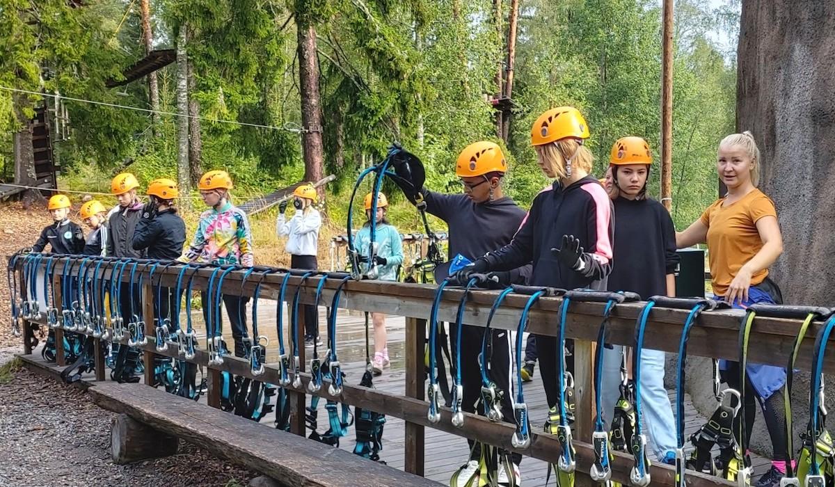 Pajulajden seikkailupuistossa. Lapset ovat pukemassa valjaita oranssit kypärät päässä pienell sillalla.