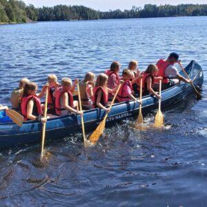Joukko lapsia melomassa kanootilla Riemuleirillä.