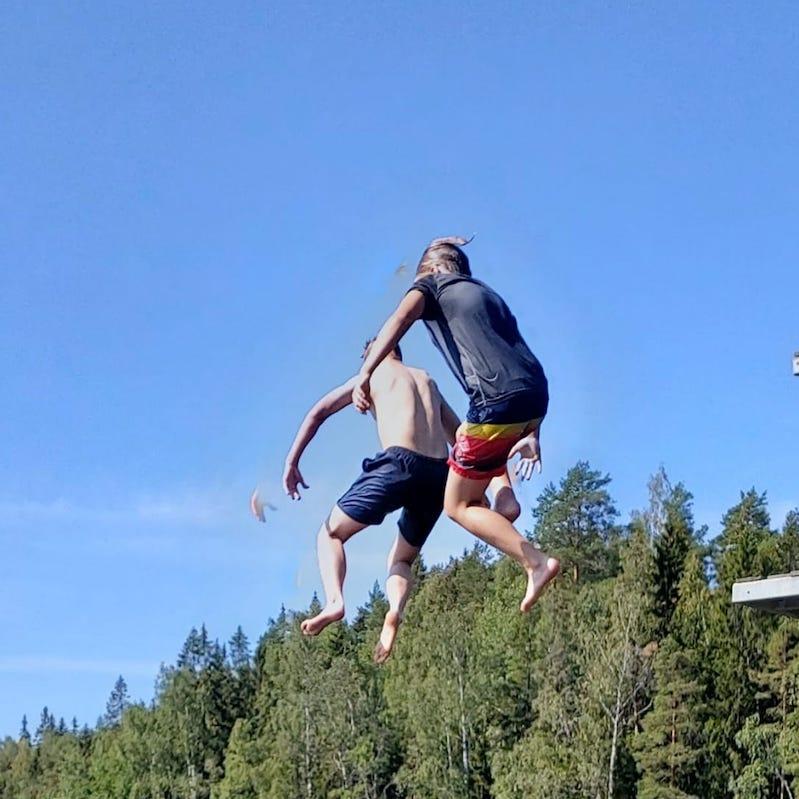 Riemuleirillä kaksi poikaa hyppäämässä järveen hyppytornista. Pojat ilmassa selin kameraan.