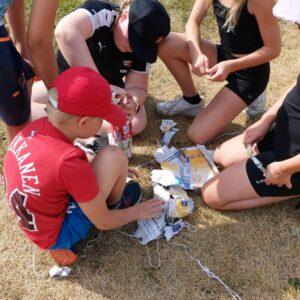 Riemuleirillä viisi lasta nurmikolla rakentamassa jotain sanomalehtipaperista.