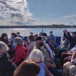 Kolmisen kymmentä ihmistä veneessä maskit päällä. Keli on aurinkoinen ja järvi tyyni.