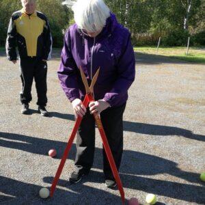 Veteraanijaoston puheenjohtaja Eeva Kurki tuomaroi boccia-kisaa. Hiekkakentällä mittaa pallojen etäisyyttä.