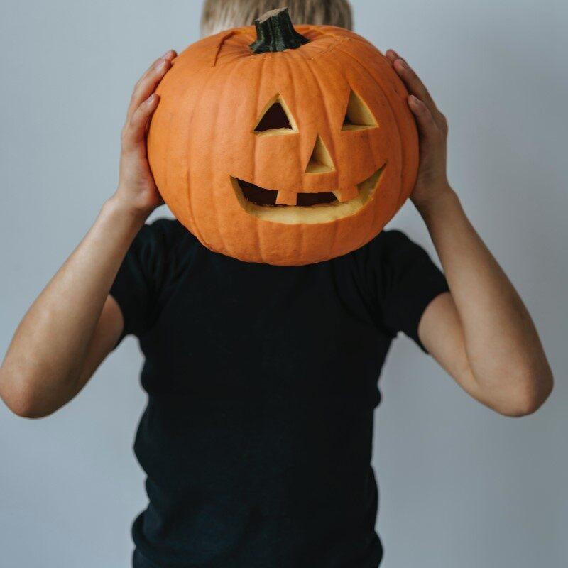 Halloween leiri. Lapsi pitää kurpitsaa naamansa edessä.
