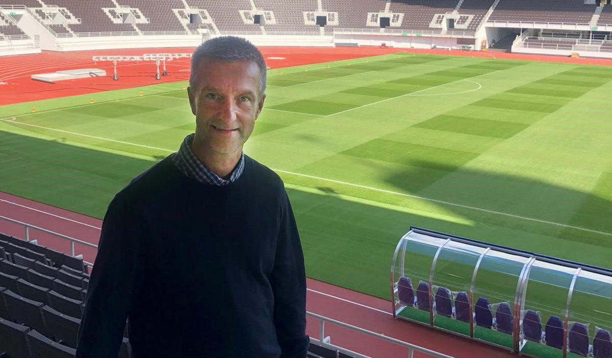 Harry Seidler seisoo jalkapallostadionin katsomossa katse kohti kameraa.