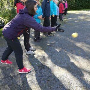 Ihmisiä hiekkakentän reunalla heittämässä tennispallon kokoistaboccia-palloa.