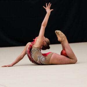 Rytmisen voimistelun esityksessä tyttö voimistelee pallon kanssa.