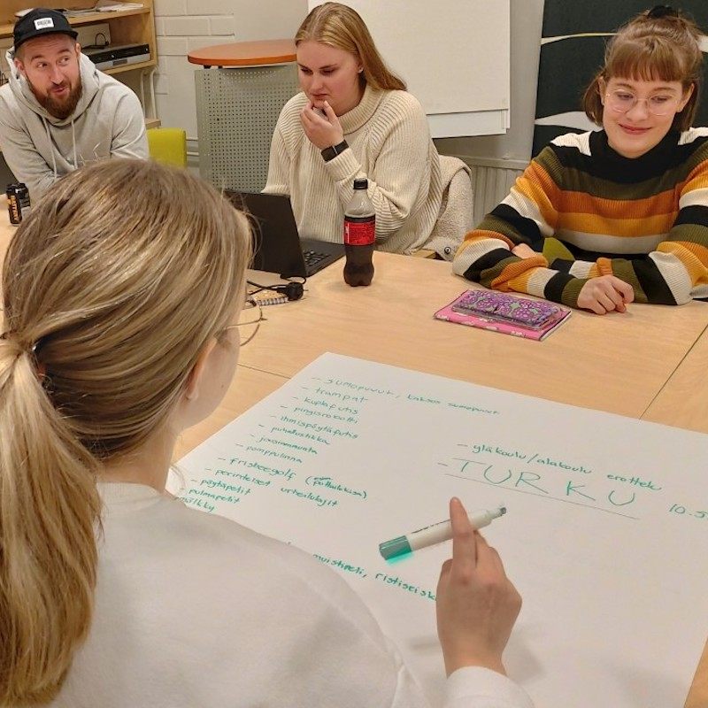 Nuoret päättäjät -koulutuksessa neljä nuorta hahmottaa paperille kehitysideoita pöydän ympärillä.