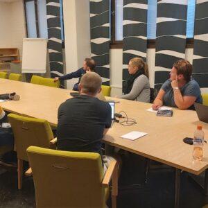 Nuore päättäjät -koulutuksessa nuoret ovat ison pöydän ympärillä kuuntelemassa naisen luentoa.