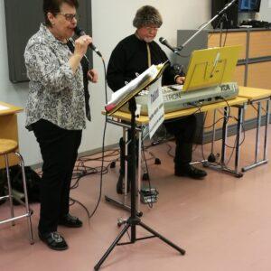 Naisoletettu laulaa mikkiin ja miesoletettu soittaa vieressä kosketinsoittimia. Tila näyttää luokkahuoneelta.
