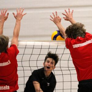 Lentopallon pelitilanne. Kaksi poikaa punaisissa paidoissa on torjumassa palloa, kun toisella puolelta on tulossa iskulyönti.